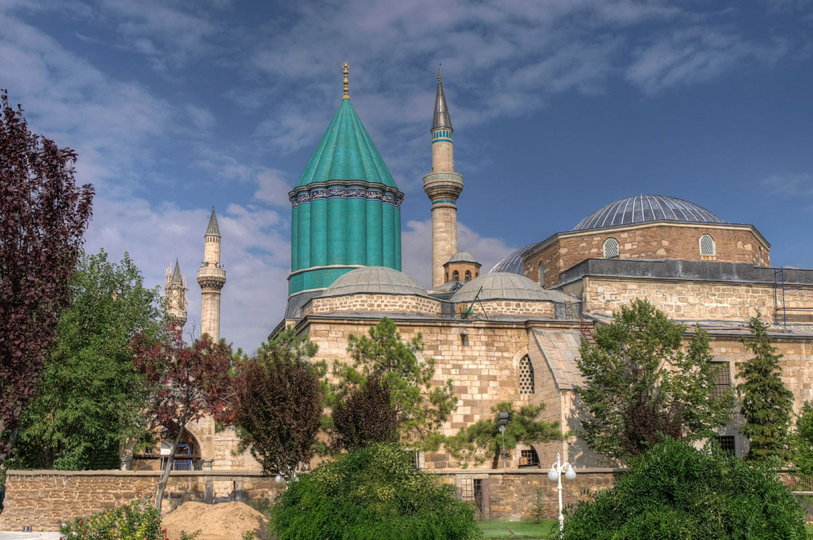 The shrine of Rumi in central Konya province comes to the forefront with its distinctive green-tiled cylindrical dome.
