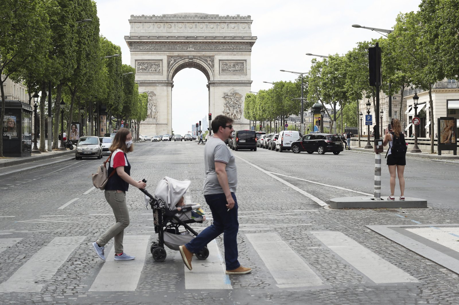 People stroll on the Champs Elysees avenue in Paris, France, June 3, 2020. (AP Photo)