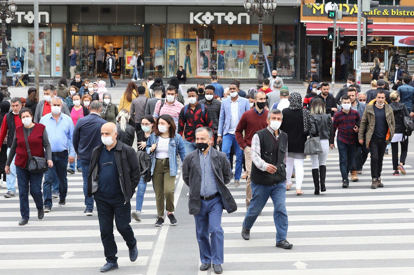 People wearing protective face masks during the coronavirus outbreak walk on a street in Ankara, Turkey, June 1, 2020. (AFP Photo)