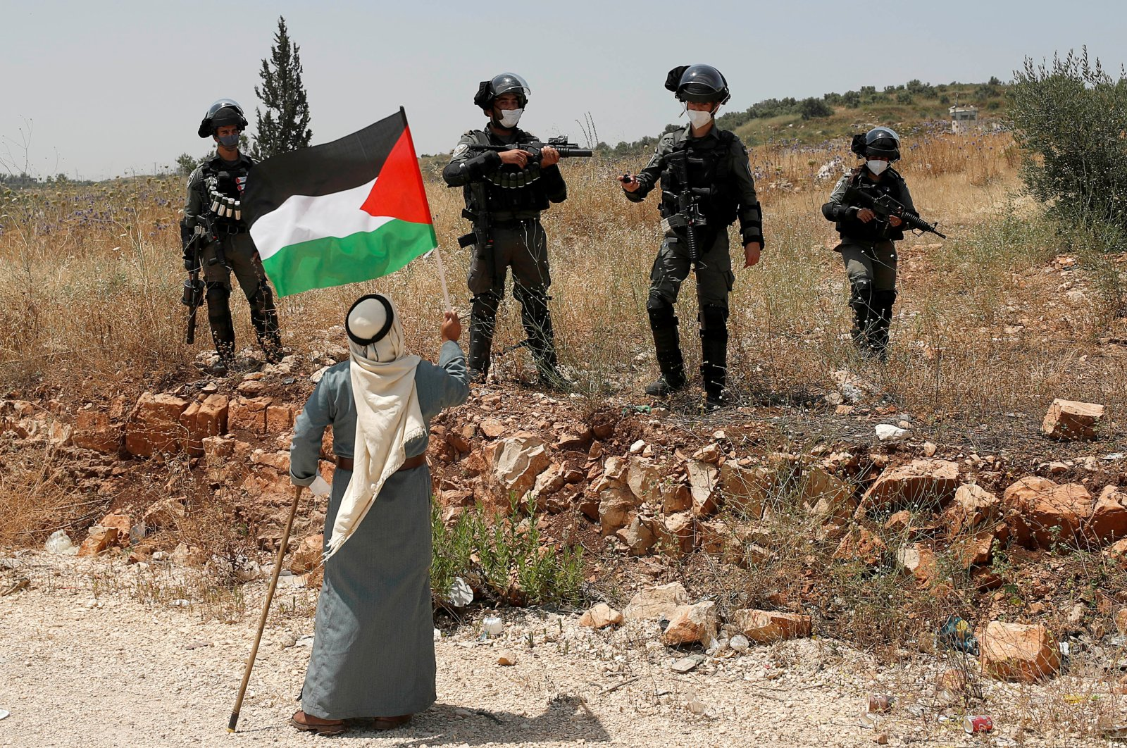 A demonstrator holds a Palestinian flag in front of Israeli forces during a protest against Israel's plan to annex parts of the occupied West Bank, near Tulkarm June 5, 2020. (Reuters Photo)