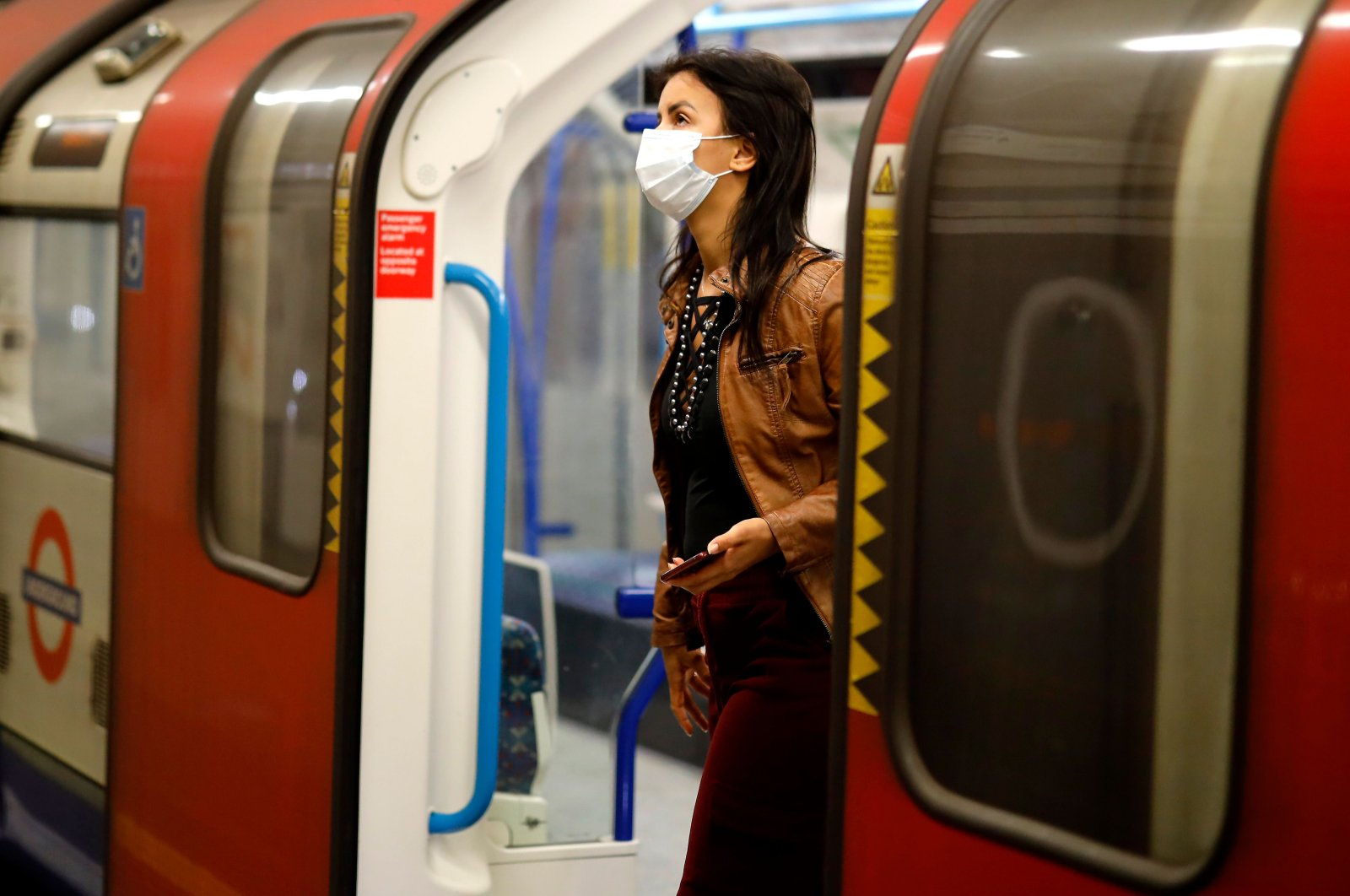 A commuter wears a facemask as she disembarks at a tube station in London on June  5, 2020. (AFP Photo)