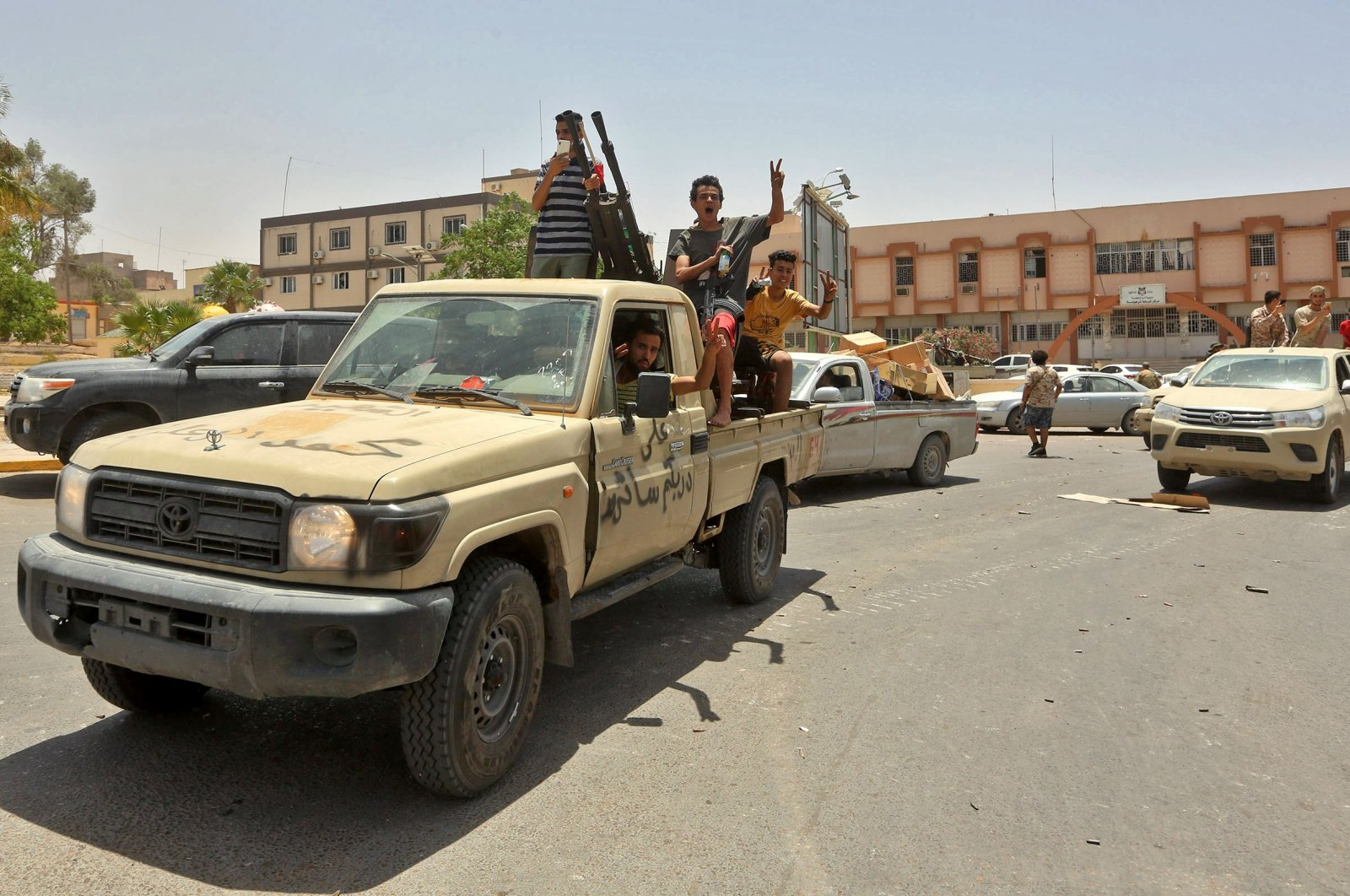Fighters loyal to Libya's U.N.-recognised Government of National Accord (GNA) pose for a picture in the back of a technical (pickup truck mounted with turret) in the town of Tarhuna, about 65 kilometers southeast of the capital Tripoli, June 5, 2020. (AFP Photo)
