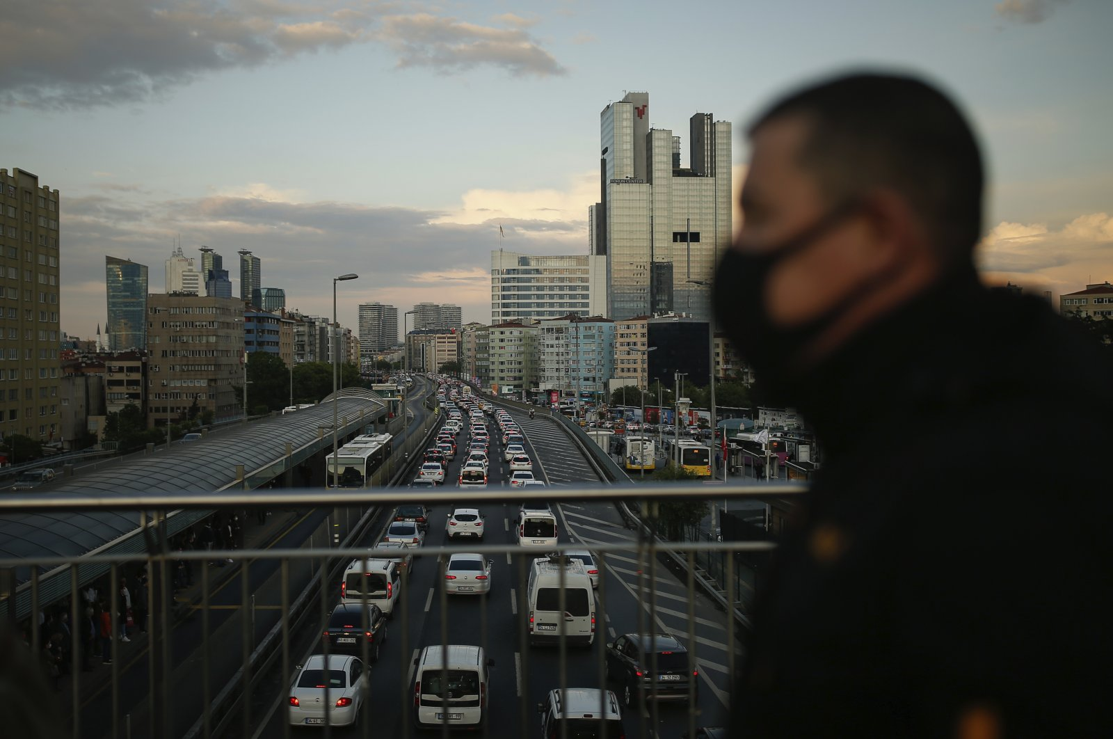 A man, wearing a protective face mask walks on a bridge amid a traffic jam during rush hour, following weeks of closures due to the coronavirus pandemic in Istanbul, June 1, 2020. (AP Photo)