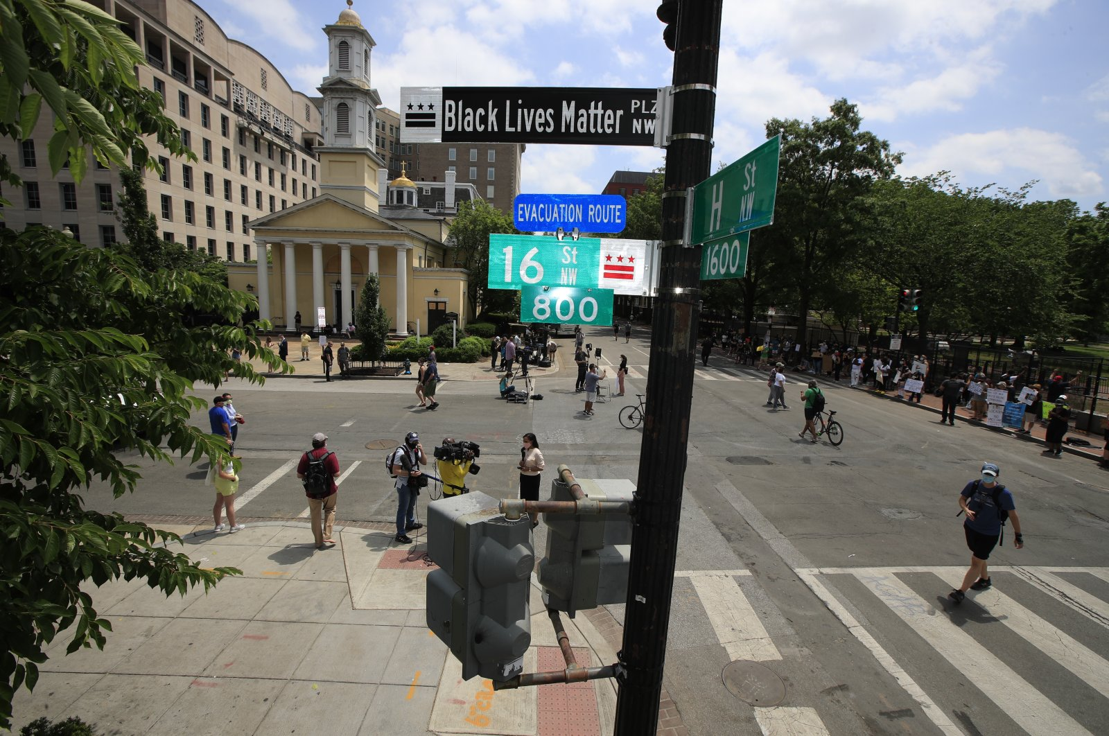 With St. John's Church in the background, people walk under a new street sign, Washington D.C. June 5, 2020. (AP Photo)