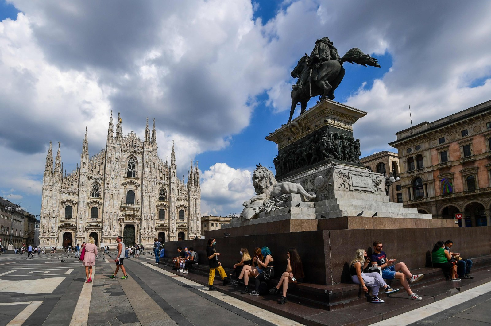 People sit on Piazza del Duomo by the cathedral in downtown Milan, aöid easing lockdowns aimed at curbing the spread of the COVID-19 infection, Milan, Italy, June 3, 2020. (AFP Photo)
