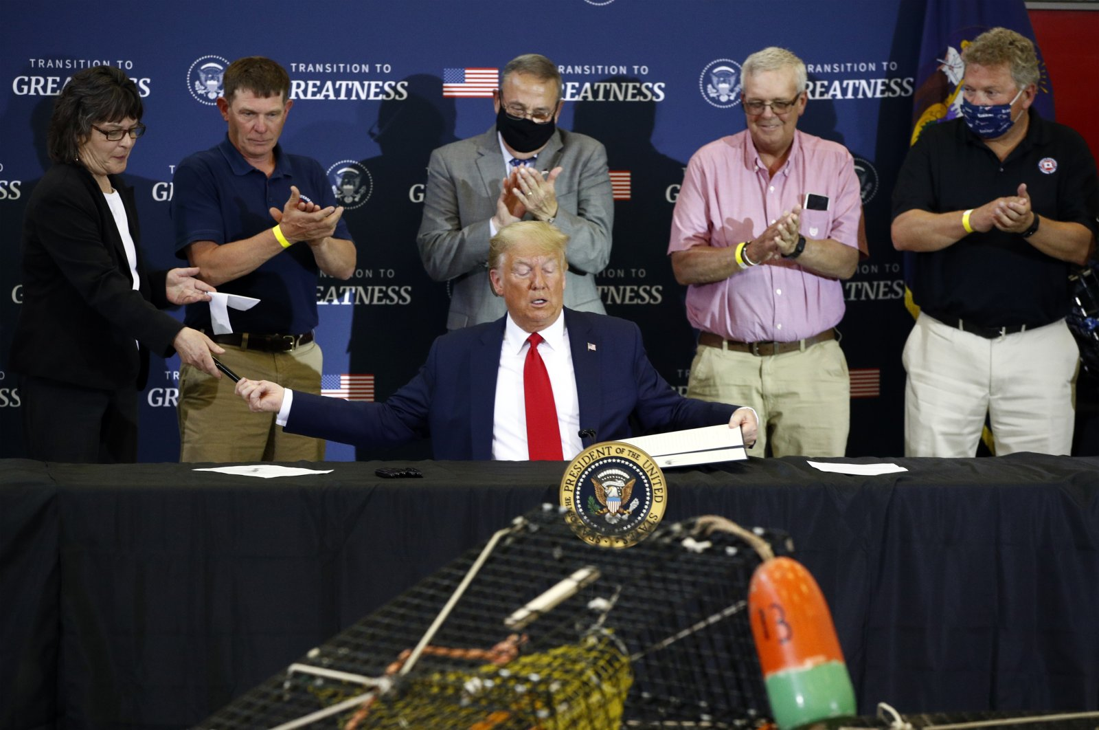 President Donald Trump hands pens out after signing an executive order on commercial fishing after speaking at a roundtable discussion with commercial fishermen at Bangor International Airport in Bangor, Maine, June 5, 2020. (AP Photo)