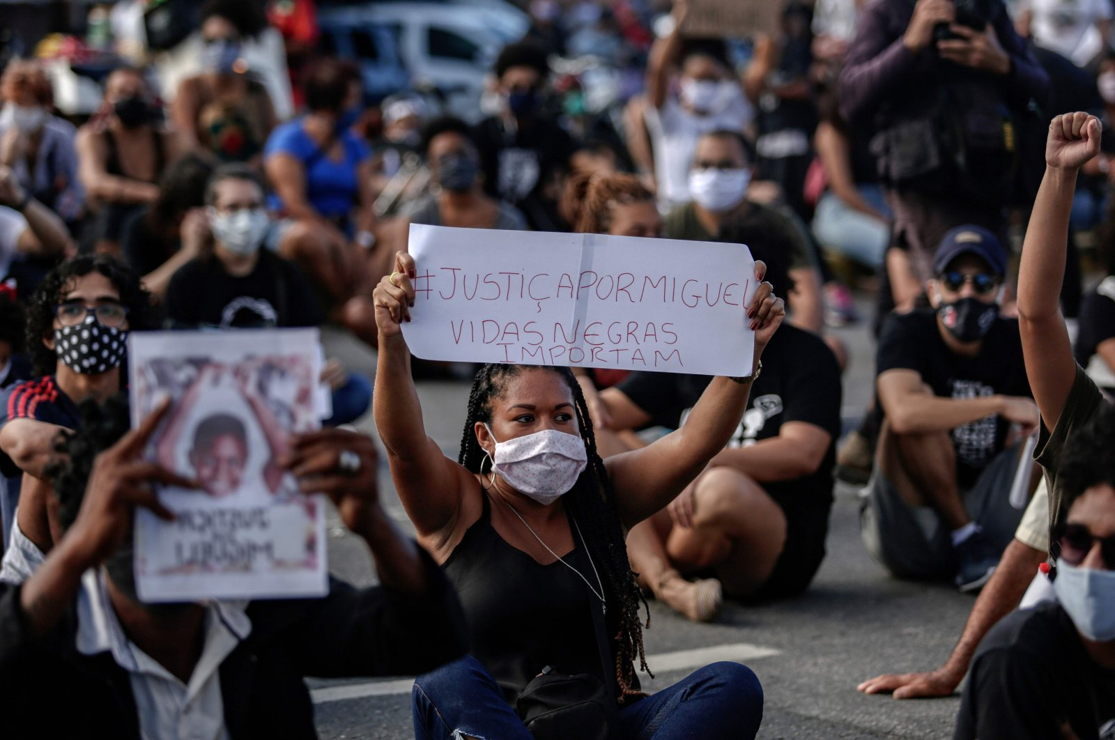 """A woman holds a sign reading """"Justice for Miguel. Black Lives Matter"""" during a demonstration in demand of justice for the death of five-year-old Miguel da Silva, the son of a black maid who on June 2 fell from the ninth floor of a building while under the watch of his mother's white employer, in Recife, Pernambuco State, in northeastern Brazil, on June 5, 2020. (AFP Photo)"""