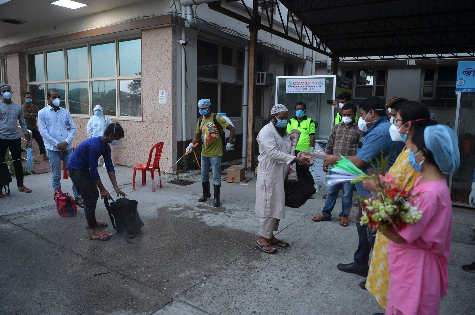 Recovered COVID-19 patients collect certificates from hospital staff as they leave a hospital in Siliguri on June 2, 2020. (AFP Photo)