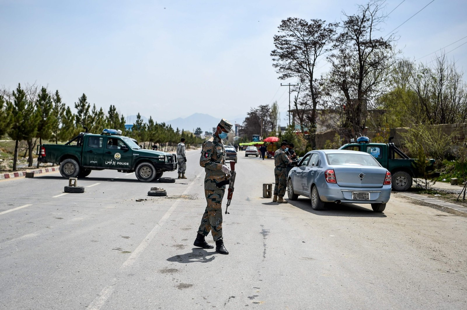 In this file photo taken on April 8, 2020, security personnel wearing facemasks stop motorists at a checkpoint during a government-imposed lockdown in Kabul. (AFP Photo)