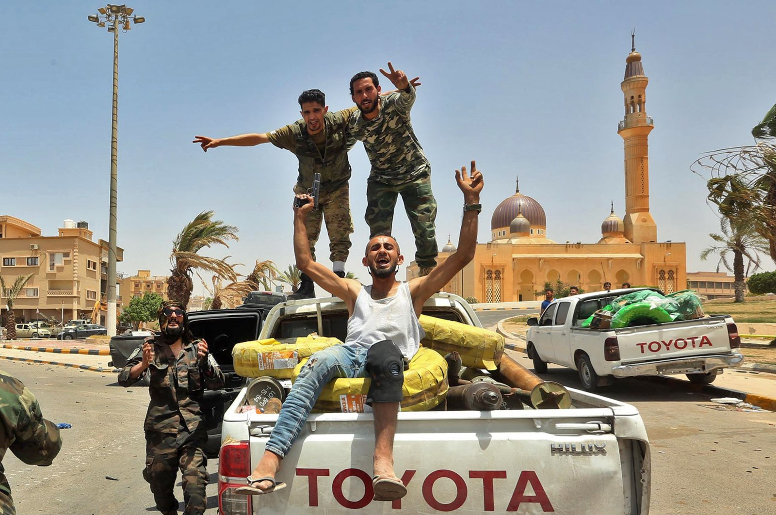 Fighters loyal to Libya's U.N.-recognized Government of National Accord (GNA) pose for a picture in the back of a pickup truck in the town of Tarhona, 65 kilometers southeast of the capital Tripoli, June 5, 2020 (AFP Photo)