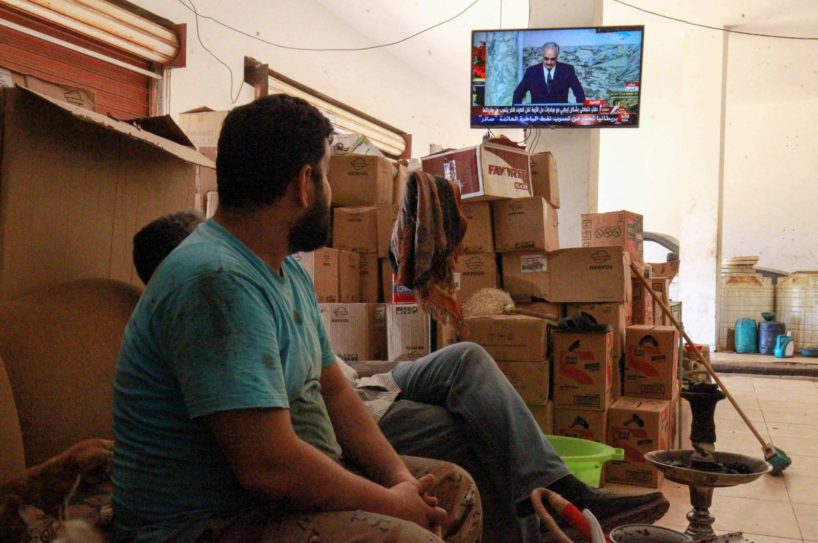 """Libyan mechanics watch a televised speech by putschist Gen. Khalifa Haftar, during the talks dubbed the """"Cairo declaration"""" at their shop in the eastern Libyan port city of Benghazi on June 6, 2020. (AFP Photo)"""