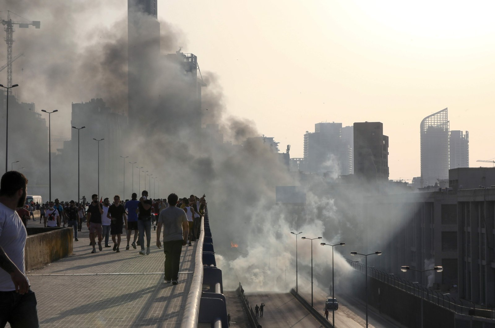 Lebanese protesters walk away from tear gas fired by riot police amid clashes following a demonstration in central Beirut on June 6, 2020. (AFP Photo)