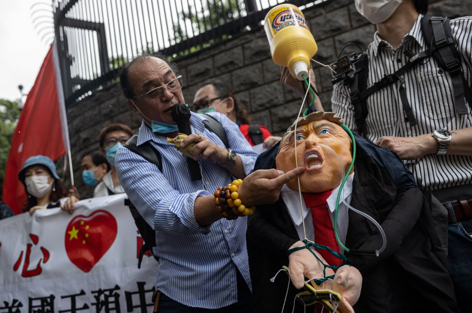 Protesters display banners and a doll of Donald Trump hooked up to a bottle of bleach during a rally outside the U.S. Consulate General in Hong Kong, China, May 30, 2020. (EPA Photo)