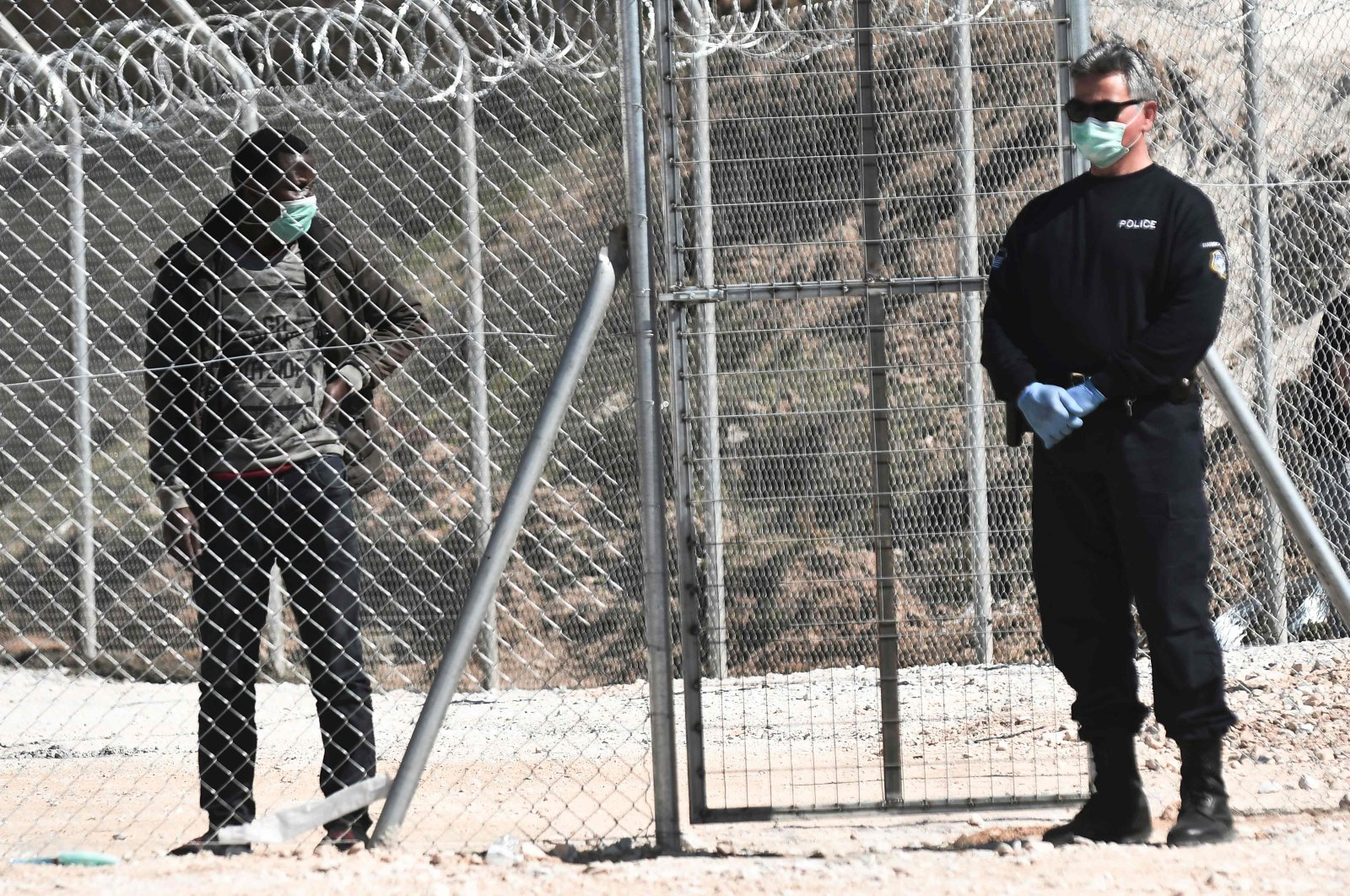 A migrant looks at a Greek police officer at a closed camp at Kleidi near Promahonas, northern Greece, March 21, 2020. (AFP Photo)