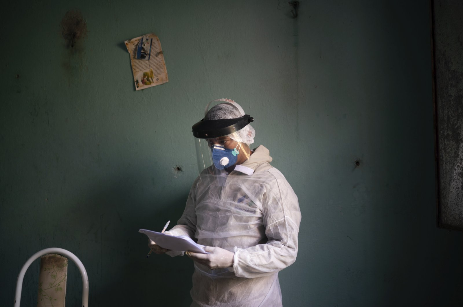 A health worker takes notes as he prepares to collect material for a COVID-19 test on an elderly woman, Manacapuru, Brazil, June 3, 2020. (AP Photo)