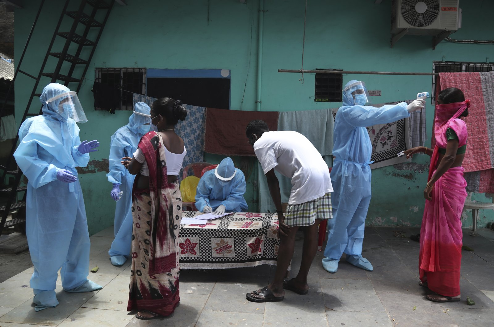 Doctors examine people during a free medical camp, Dharavi, Mumbai, India, June 7, 2020. (AP Photo)