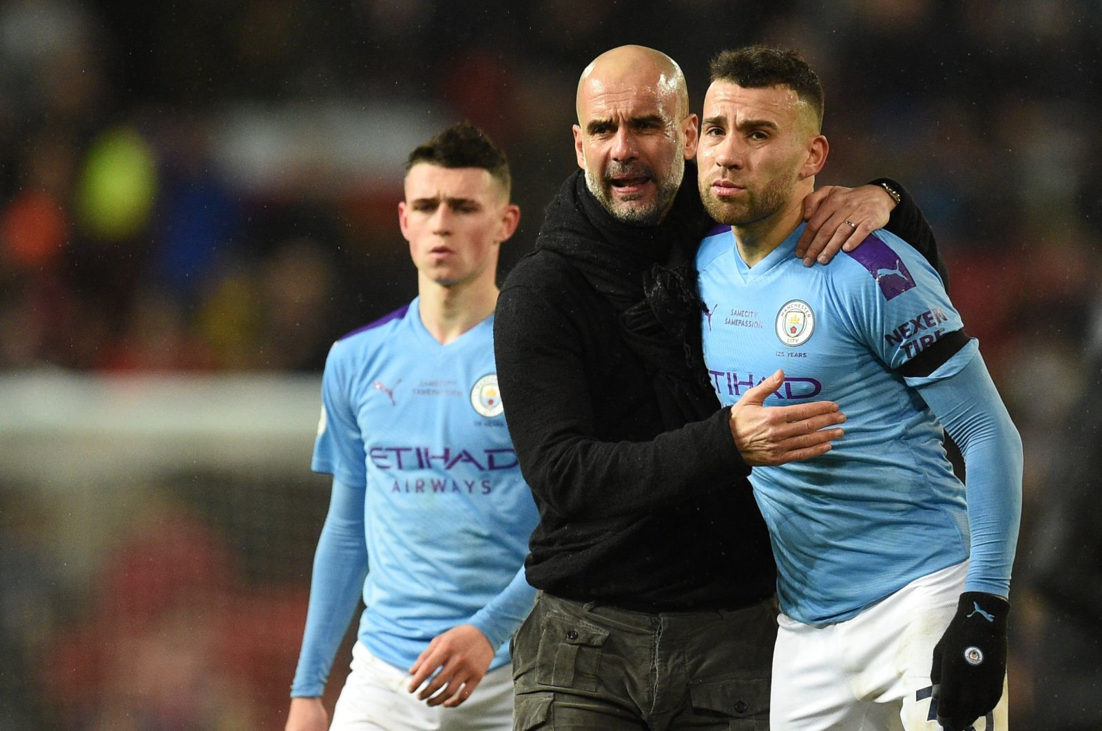 Manchester City's Phil Foden (L), Manager Pep Guardiola (C) and Nicolas Otamendi (R) react after losing to Manchester City, Manchester, England, March 8, 2020. (AFP Photo)