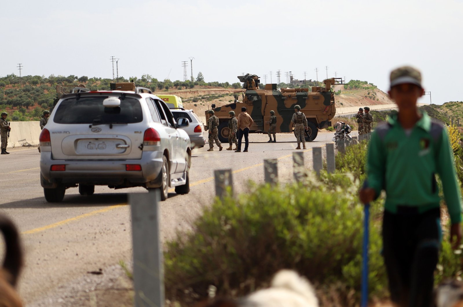 A shepherd boy leads his flock near Turkish soldiers standing outside an armored vehicle, part of a joint Turkish-Russian military patrol, along the M4 highway in Ariha in the opposition-held northwestern Syrian province of Idlib, June 2, 2020. (AFP Photo)