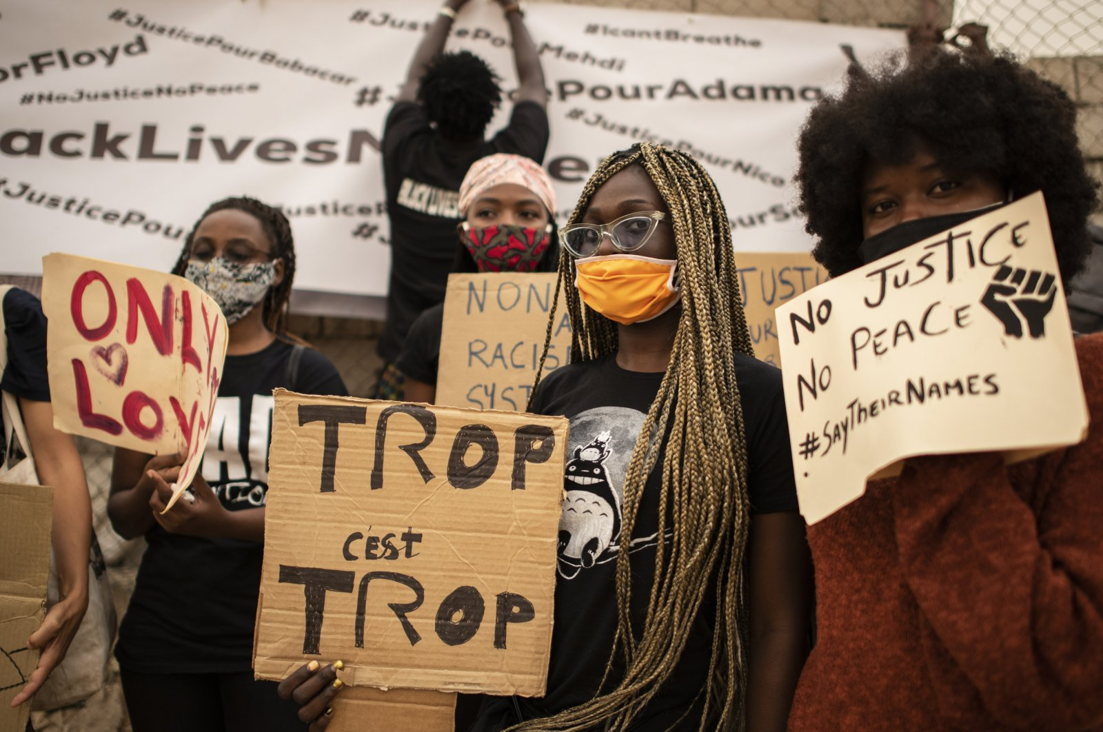 Protesters hold placards in front of the African Renaissance Monument, Dakar, June 6, 2020. (AP Photo)