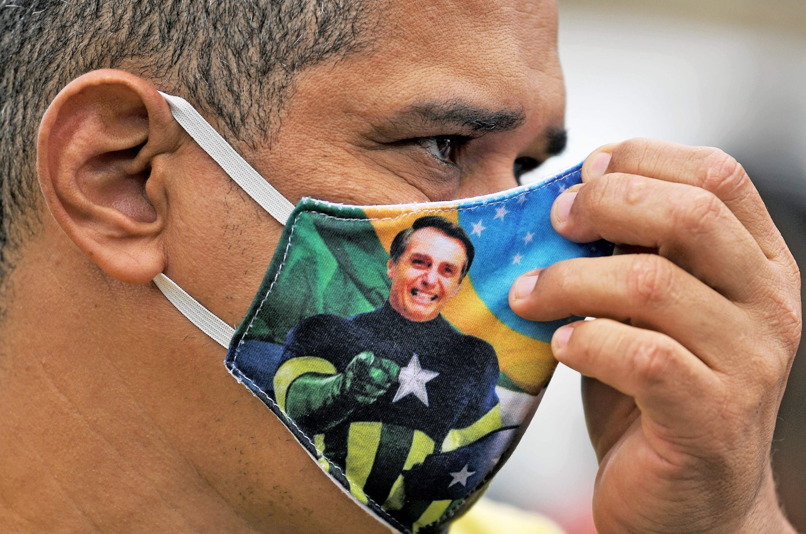 A supporter of President Jair Bolsonaro wears a face mask with Bolsonaro's image during a demonstration at Copacabana beach in Rio de Janeiro, Brazil, on June 7, 2020. (AFP Photo)