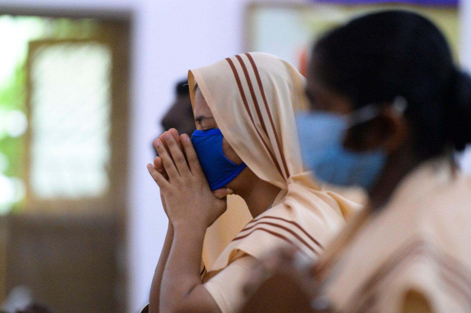 A Catholic nun wearing a face mask attends a Mass service at Saint Joseph's Church, Hyderabad, India, June 8, 2020. (AFP Photo)