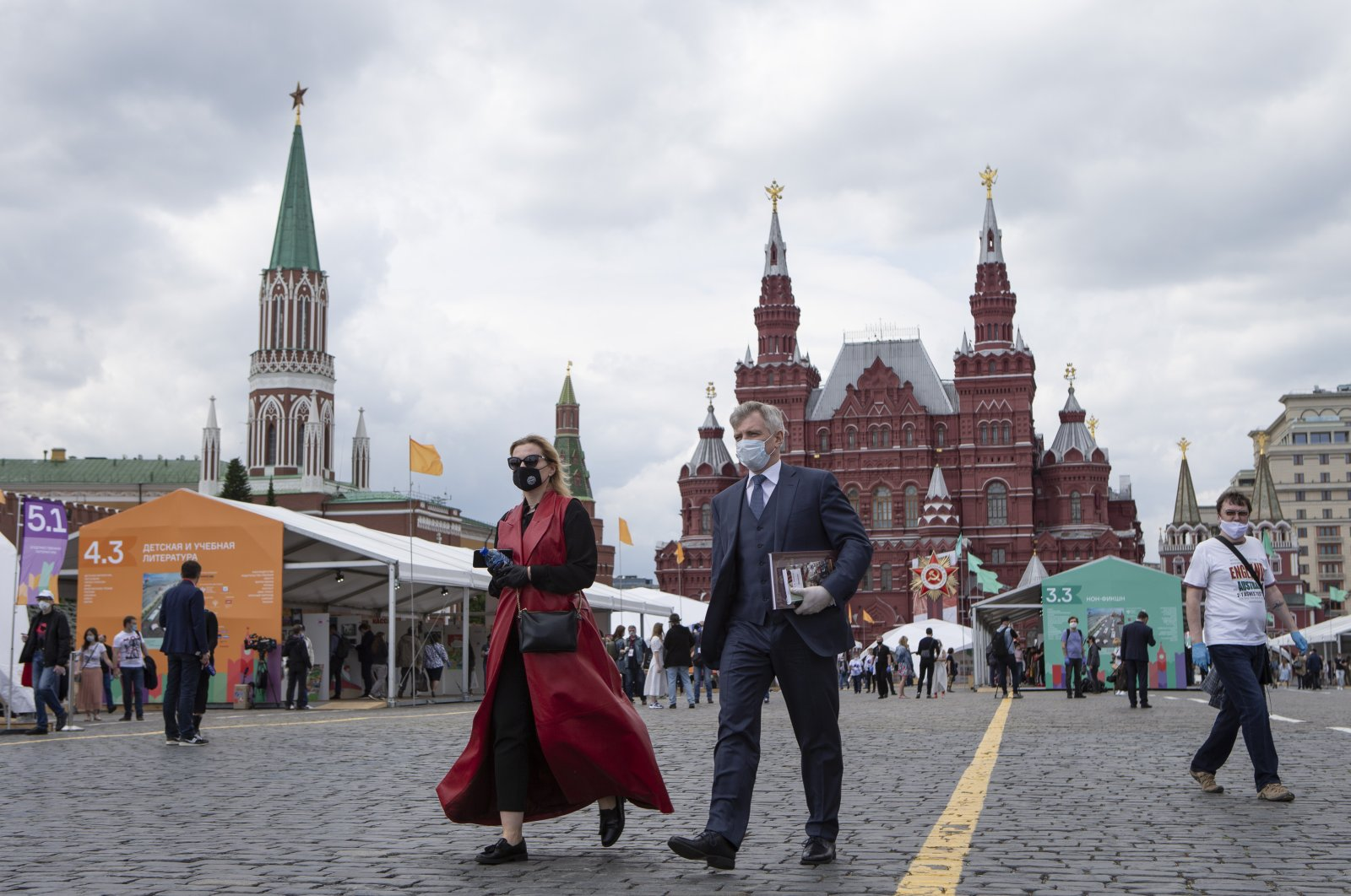 People wearing face masks to protect against the coronavirus walk at an outdoor book market set up in the Red Square with a historical museum in the background, Moscow, Russia, June 6, 2020. (AP Photo)