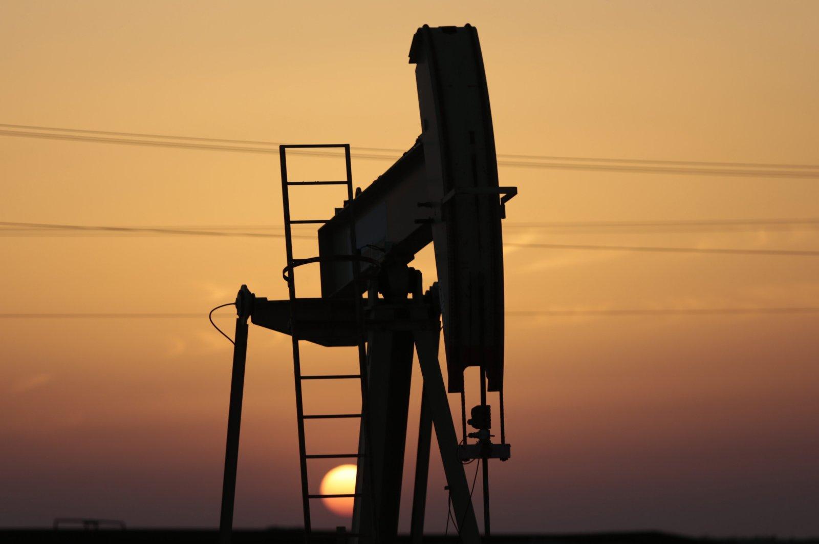 An oil pump works at sunset in the desert oil fields of Sakhir, Bahrain, April 16, 2016. (AP Photo)