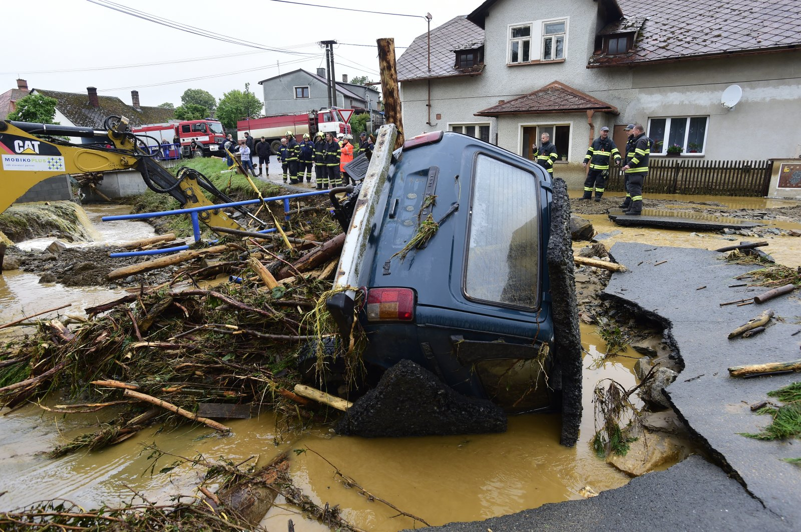 A car is trapped in a flooded area in Brevenec, the part of the village of Sumvald in the Olomouc region, Czech Republic, June 8, 2020. (AP Photo)