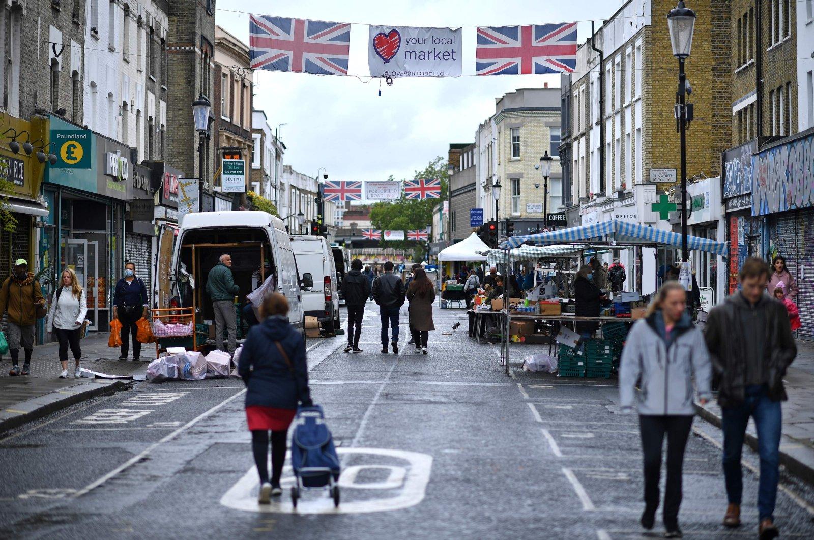 People walk past stalls at an almost deserted Portobello Road Market, London, June 6, 2020. (AFP Photo)