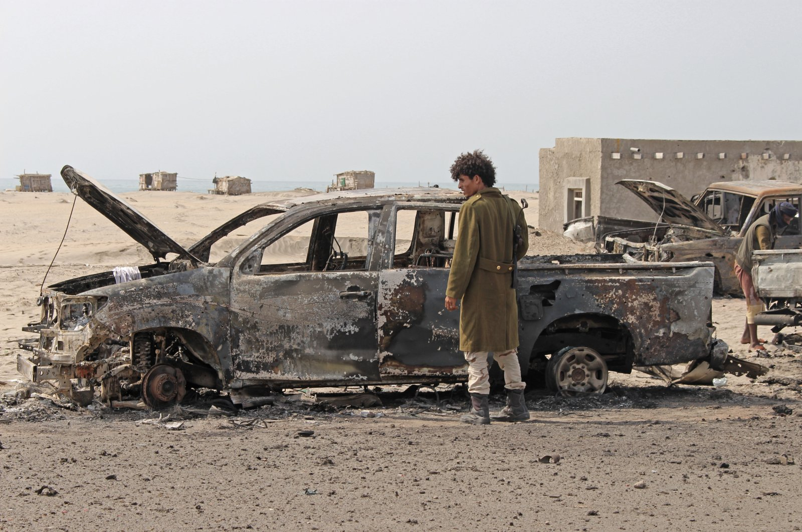 A Yemeni southern separatist fighter inspects the wreckage of government forces vehicles destroyed by UAE airstrikes, Aden, Aug. 30, 2019. (AP Photo)
