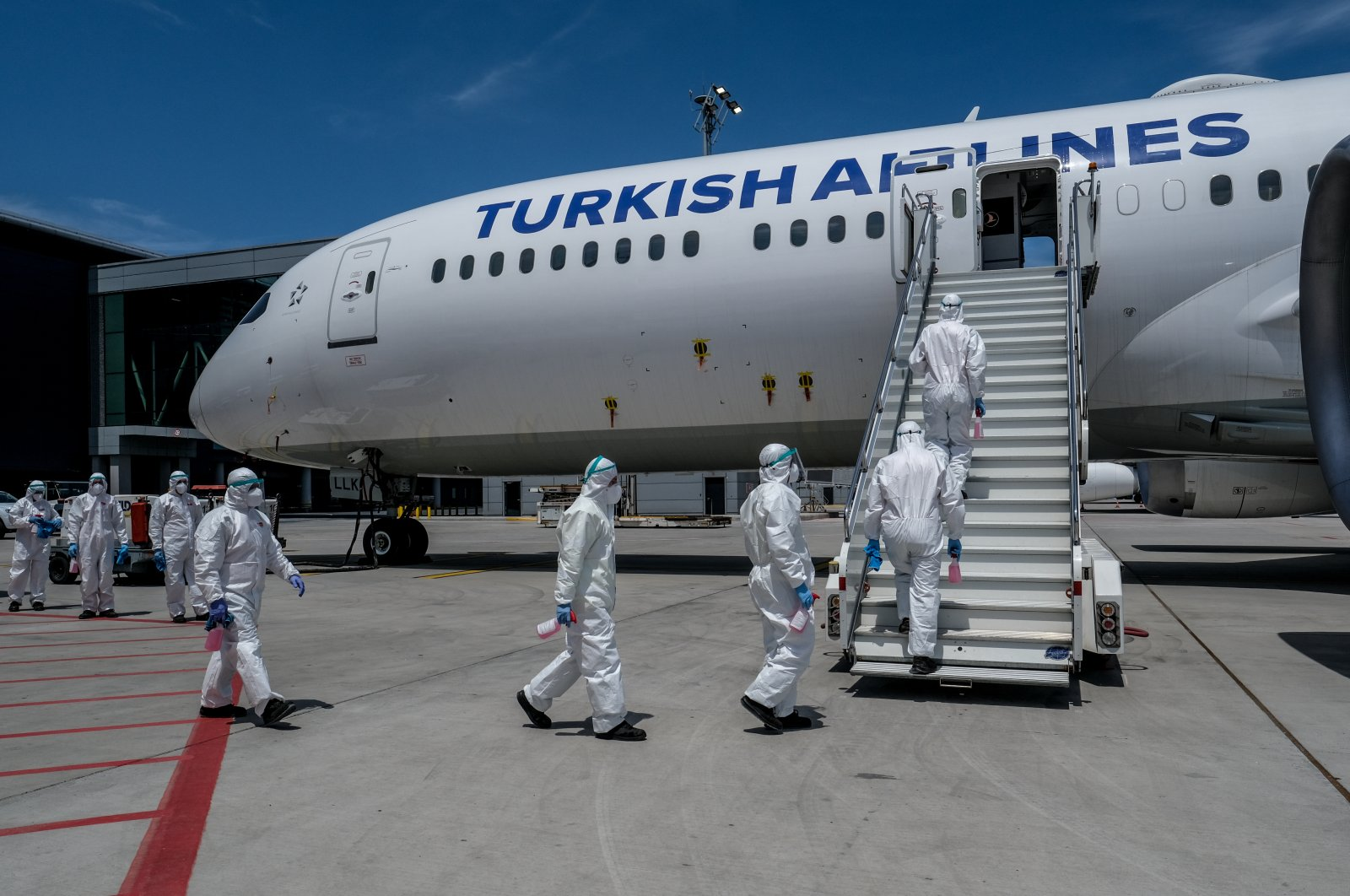 Workers enter a Turkish Airlines plane for disinfection in Istanbul, Turkey, June 2, 2020. (PHOTO BY UĞUR YILDIRIM)