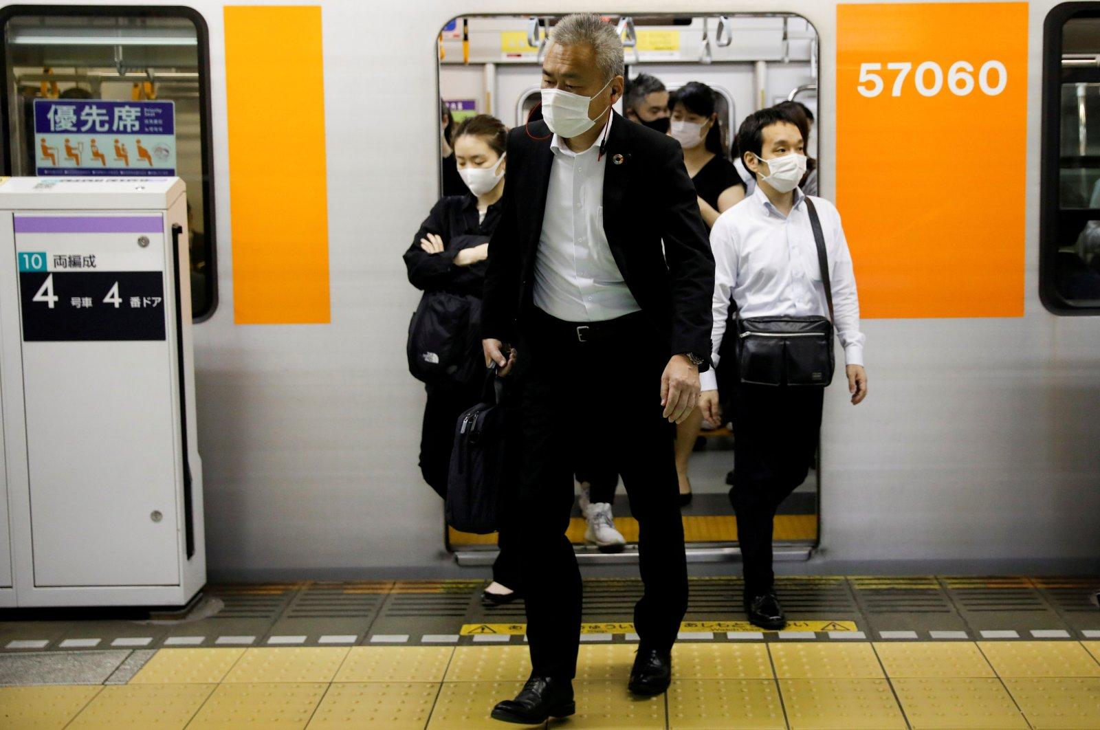 Passengers wearing protective masks get off a subway train at Shibuya station amid the coronavirus outbreak in Tokyo, Japan, May 27, 2020. (Reuters Photo)