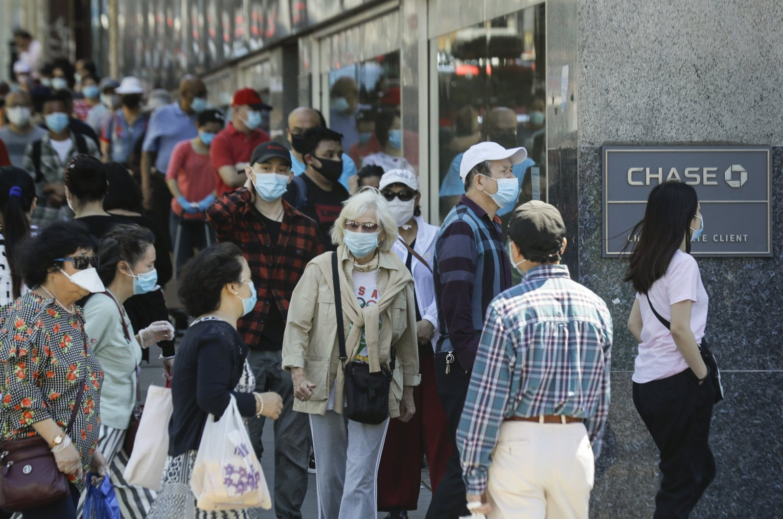 Patrons wearing protective masks wait to enter a Chase Bank location in the Flushing section of the Queens borough of New York City, New York, U.S., June 8, 2020. (AP Photo)