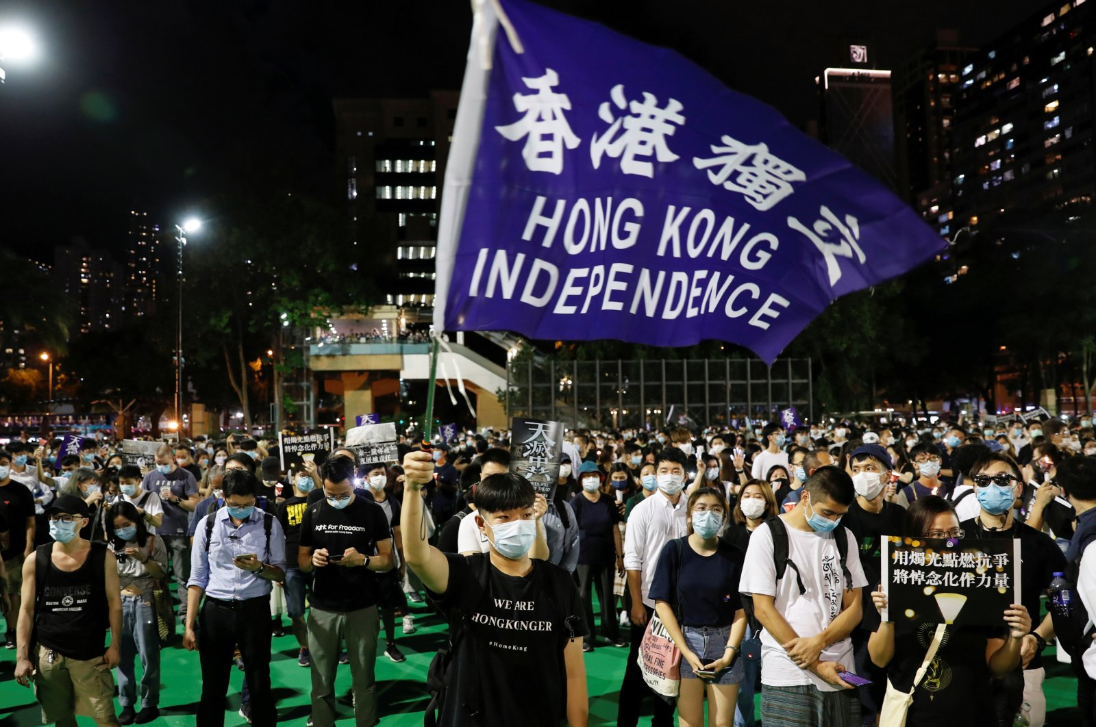 A person wearing protective face mask waves a Hong Kong independence flag as protesters take part in a candlelight vigil to mark the 31st anniversary of the crackdown of pro-democracy protests at Beijing's Tiananmen Square in 1989, after police reject a mass annual vigil on public health grounds, at Victoria Park, in Hong Kong, China June 4, 2020. (Reuters Photo)