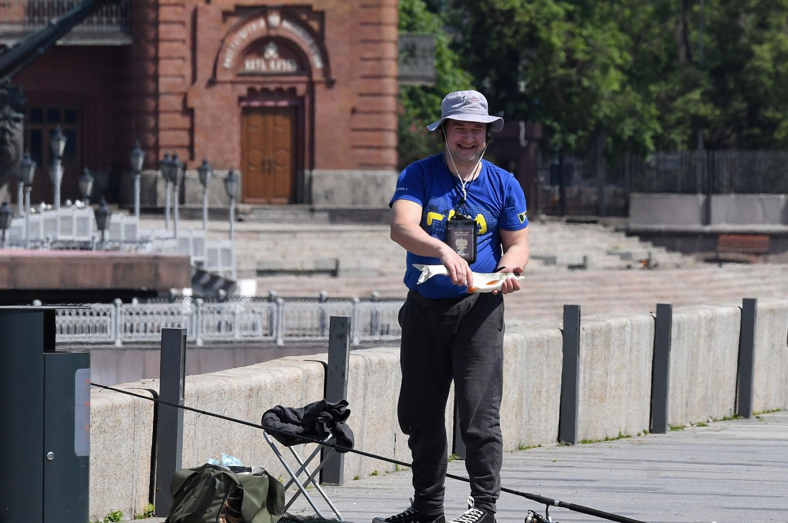 A man smiles holding his catch as he fishes at an embankment of the Moskva river in downtown Moscow on June 9, 2020. (AFP Photo)