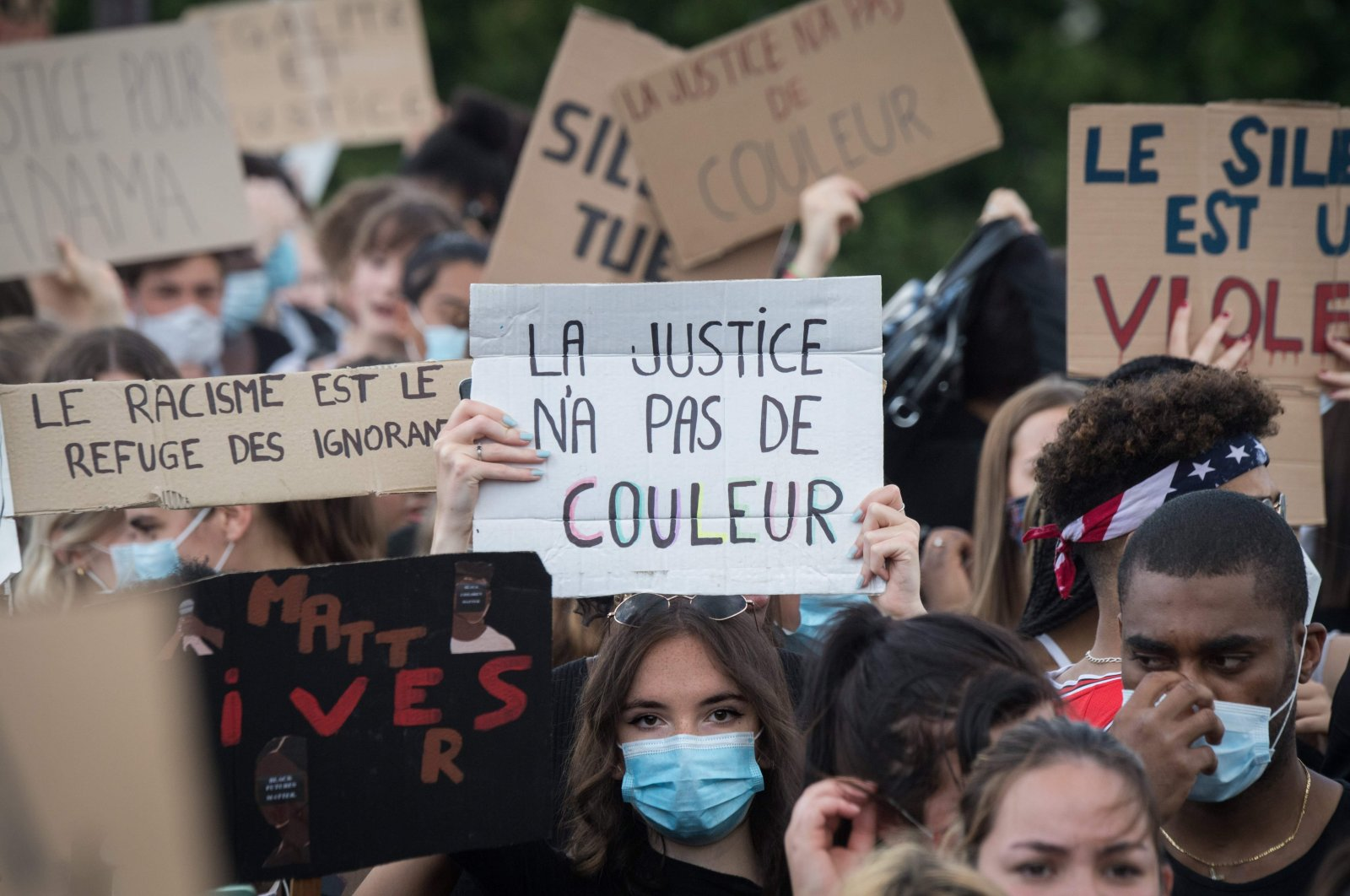 """A woman wearing a protective face mask holds a placard reading """"Justice has no color,"""" Nantes, France, June 8, 2020. (AFP Photo)"""
