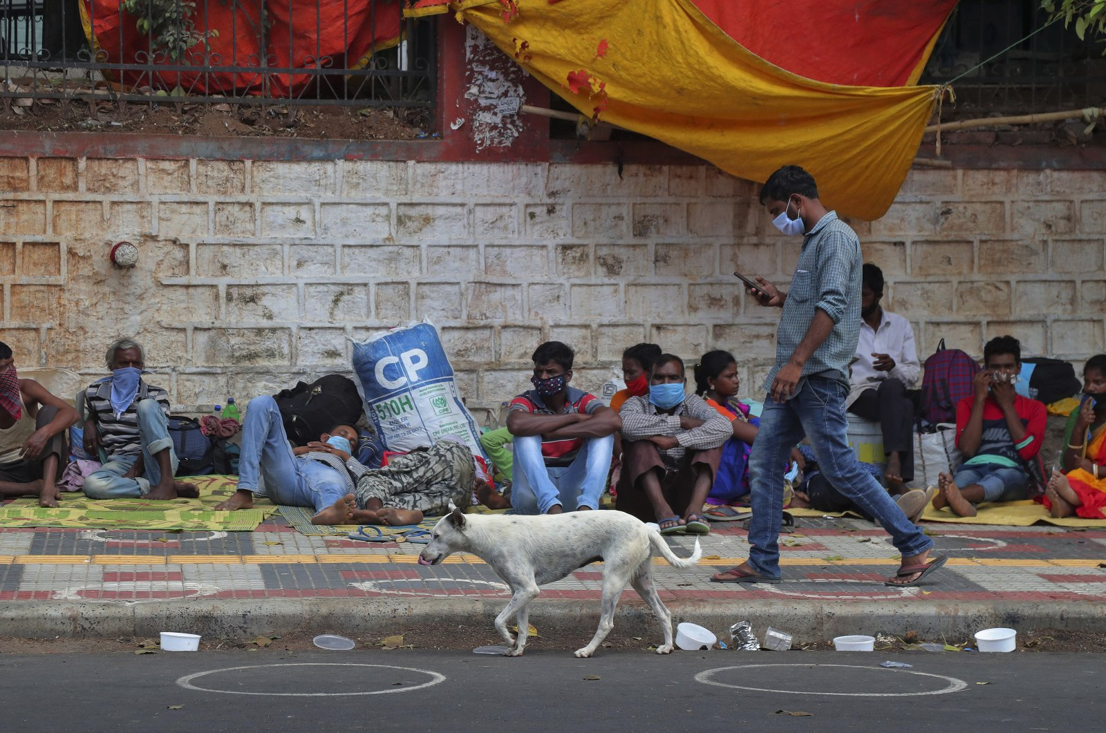 Migrant workers from other states rest on a pavement as they wait for trains to their home states, Hyderabad, India, June 9, 2020. (AP Photo)