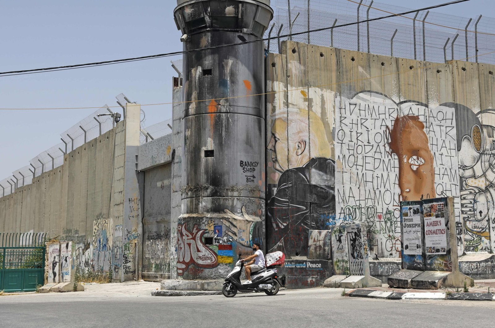 A Palestinian man rides his motorcycle past a mural painting of US President Donald Trump on Israel's controversial separation barrier in the West Bank city of Bethlehem on June 8, 2020. (AFP Photo)