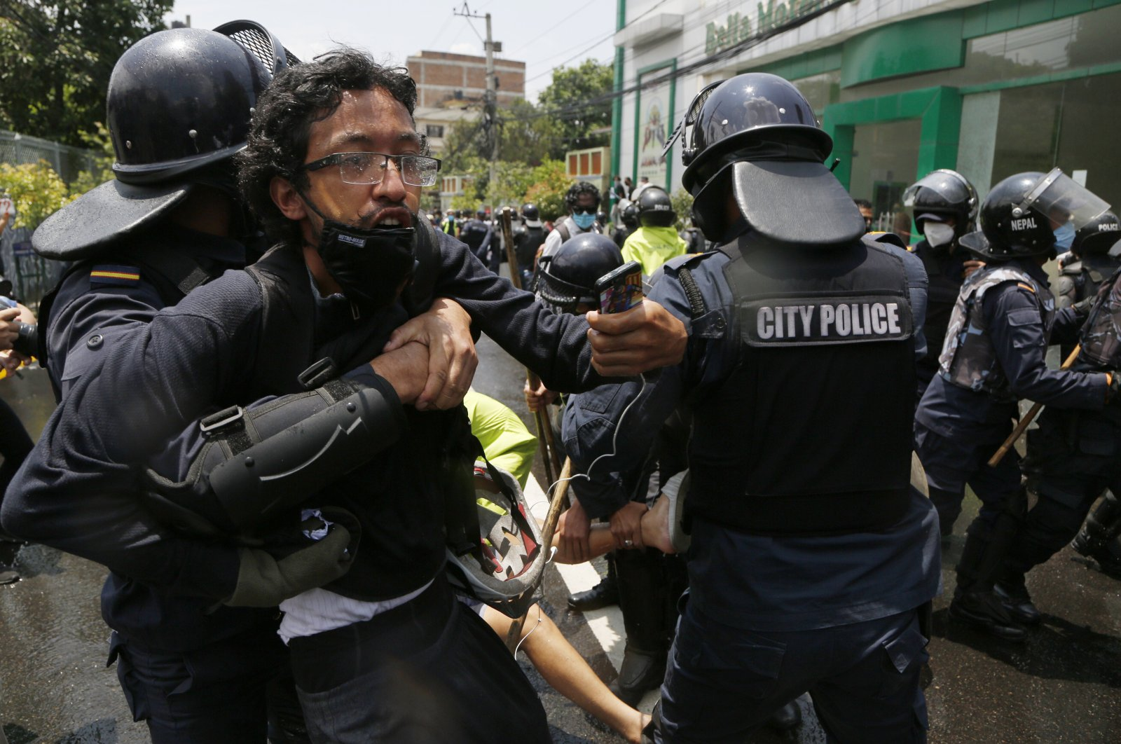Nepalese police in riot gear detain youth who were protesting on a road leading to the prime minister's official residence in Kathmandu, Nepal, June 9, 2020. (AP Photo)