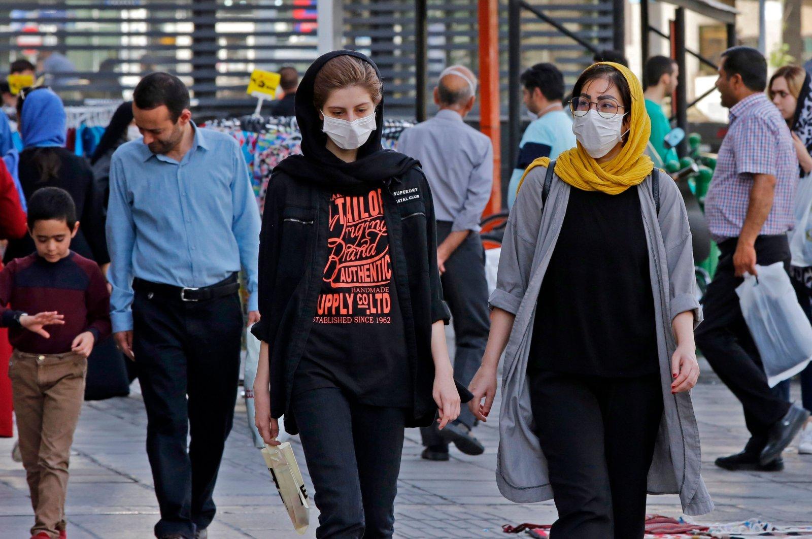 Iranians, some wearing face masks, walk along a street, Tehran, Iran, June 3, 2020. (AFP Photo)