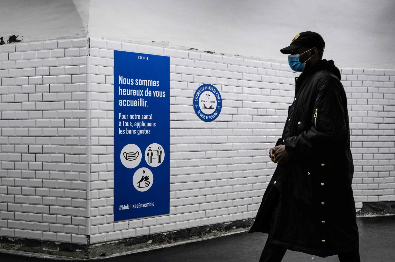 A commuter wearing a protective face mask walks past safety guideline signs in a metro station in Paris, France, May 14, 2020. (AFP Photo)