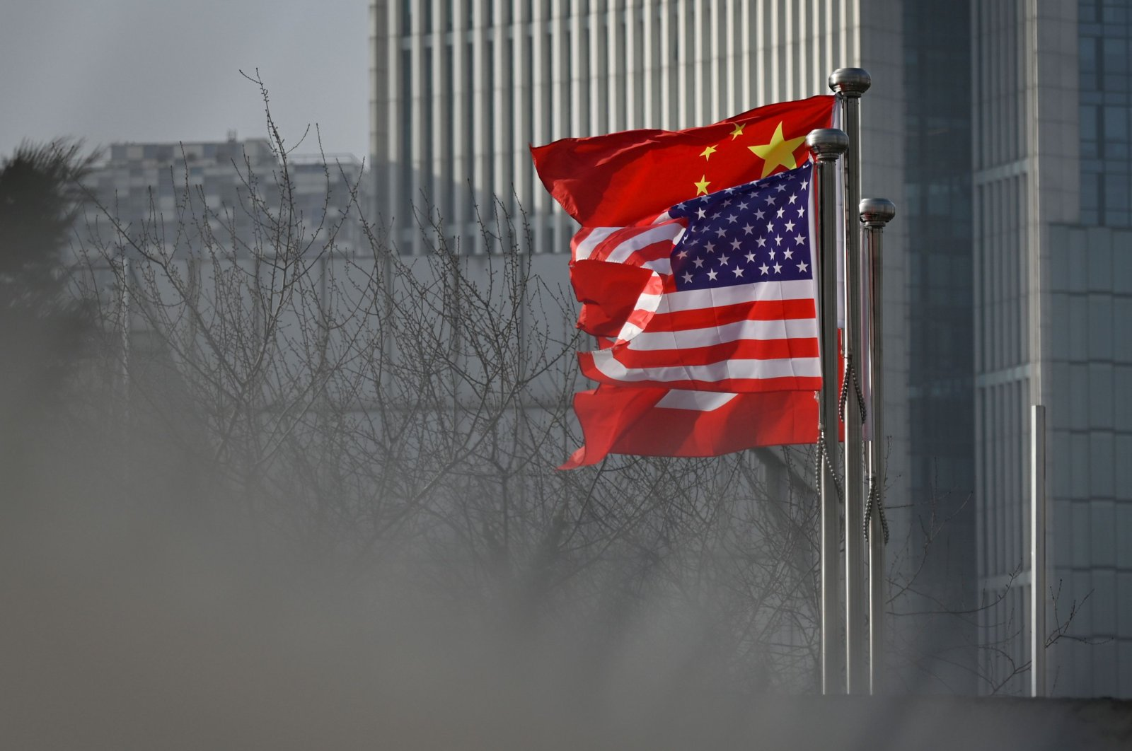 Chinese and U.S. national flags flutter at the entrance of a company office building in Beijing, Jan. 19, 2020. (AFP Photo)
