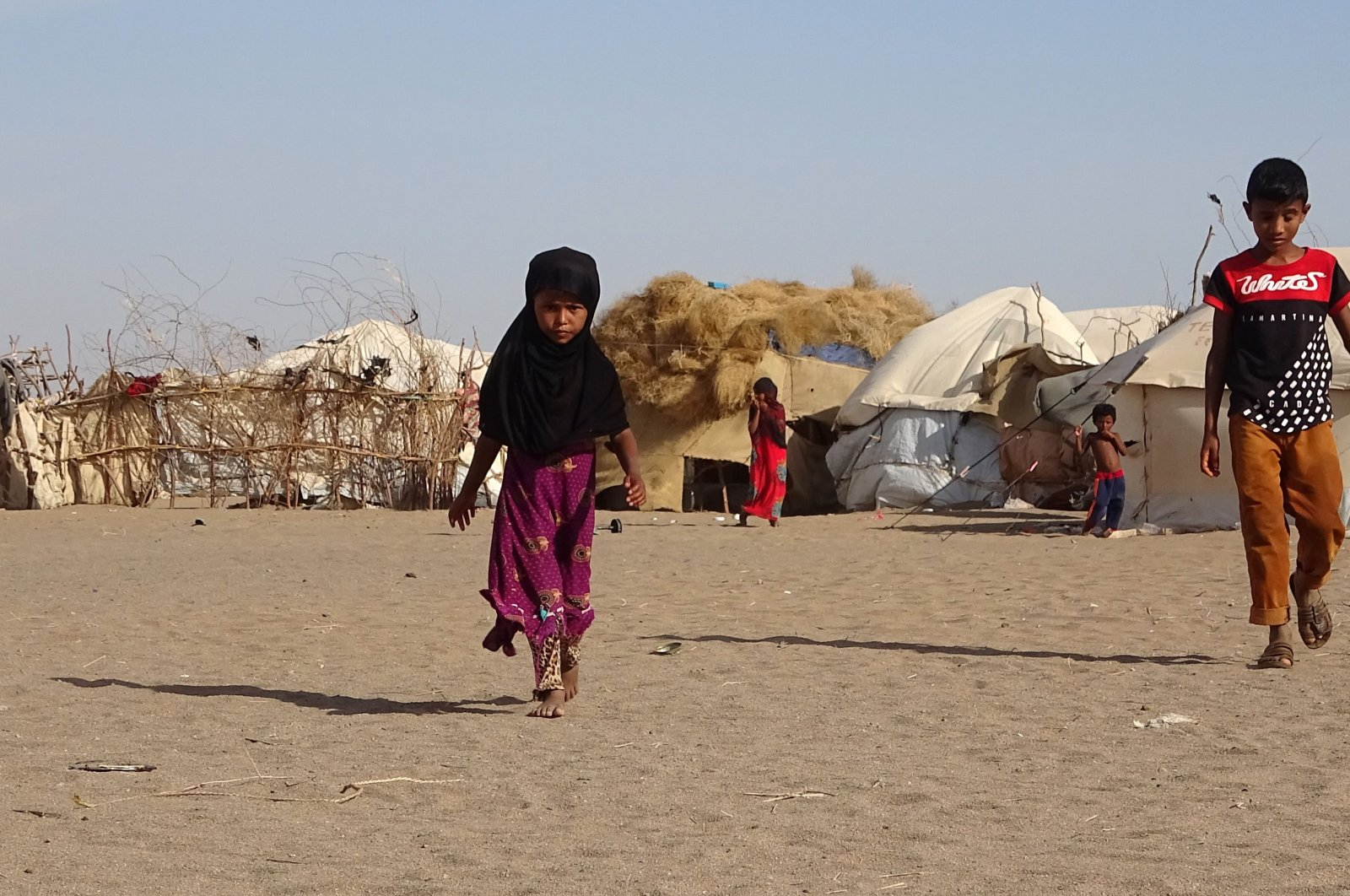 This May 6, 2020, file photo shows children walking past tents at a displaced persons camp in the Khokha district of Hodeida province, western Yemen. (AFP Photo)
