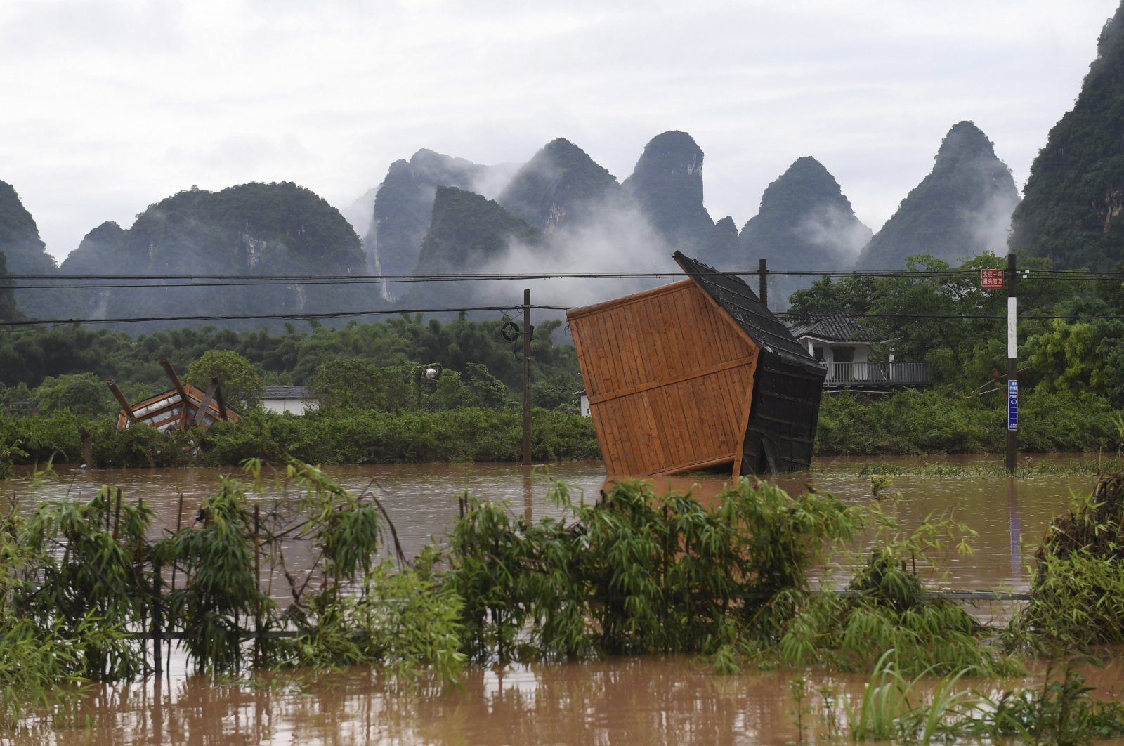 In this June 7, 2020, photo released by Xinhua News Agency, facilities at a tourism site are toppled in the aftermath of a flood after heavy downpour in Yangshuo of Guilin, south China's Guangxi Zhuang Autonomous Region. (Lu Boan/Xinhua via AP)