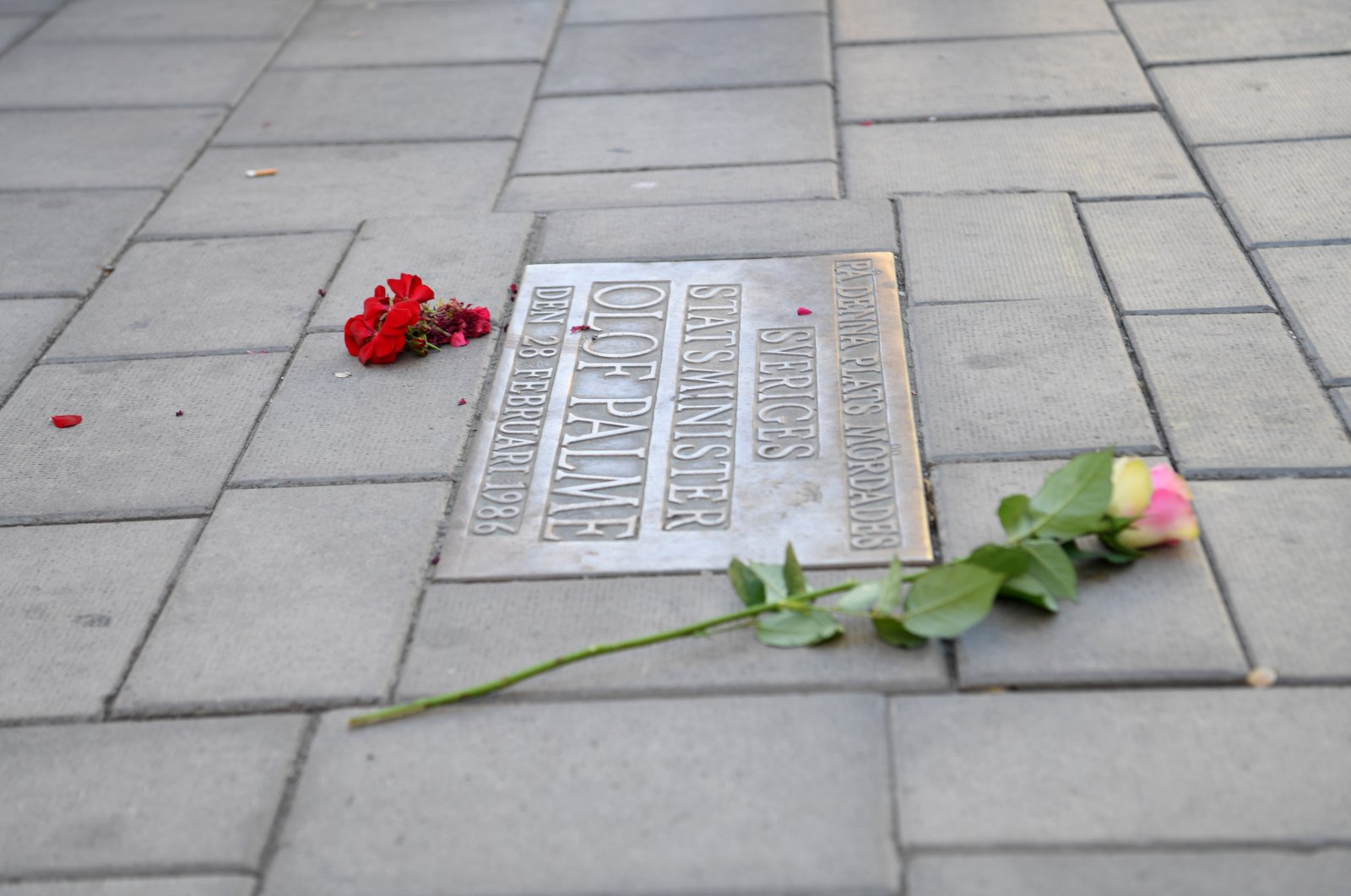 Flowers are placed by a memorial plaque showing the place where Swedish Prime Minister Olof Palme was shot dead in February 1986, in Stockholm, Sweden, Wednesday, June 10, 2020. (TT via AP)