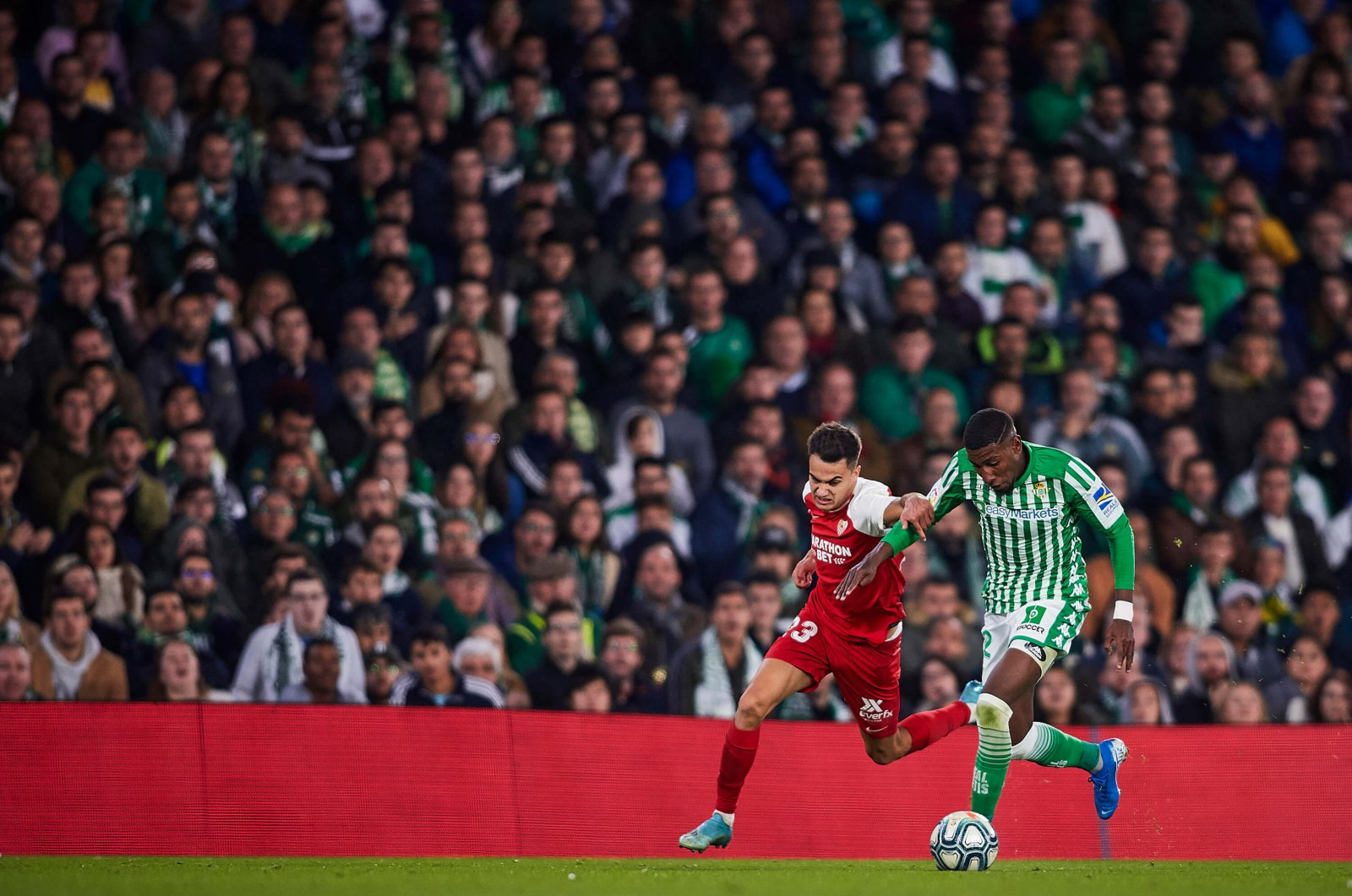 Real Betis' Emerson competes for the ball with Sevilla's Sergio Reguilon Rodriguez during a La Liga match in Seville, Spain, Nov. 10, 2019. (Photo by Quality Sport Images/Getty Images)