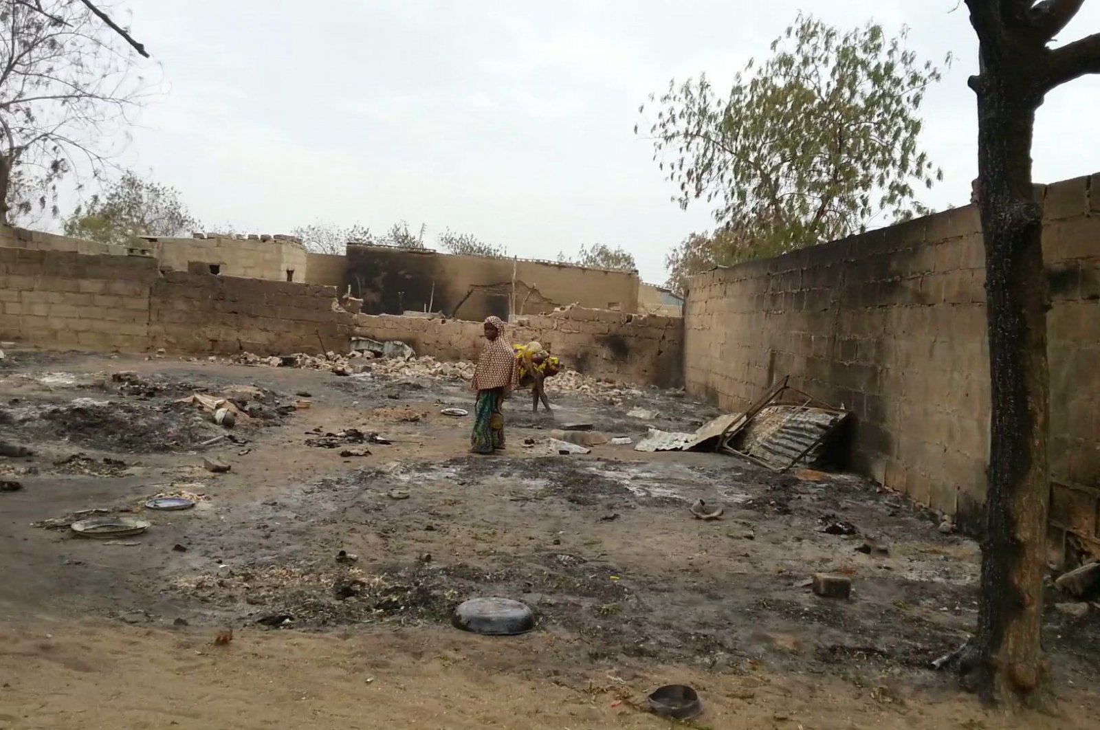 In this image shot with a mobile phone, a young girl stands amid the burned ruins of Baga, Nigeria, April 21, 2013. (AP Photo)