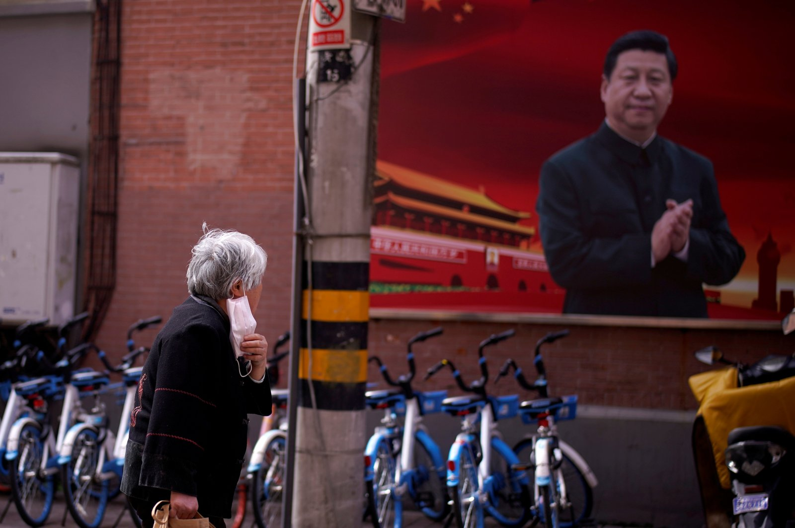 A woman with a protective mask is seen passing a portrait of Chinese President Xi Jinping on a street as the country is hit by an outbreak of the coronavirus, in Shanghai, China, March 12, 2020. (Reuters Photo)