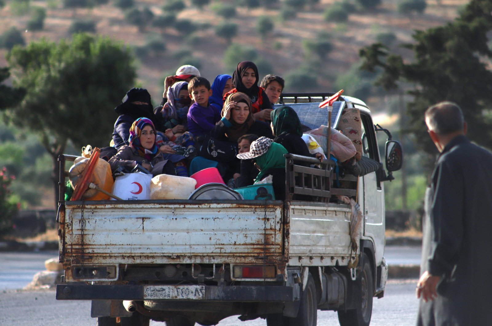 Displaced Syrians sit in the back of a truck loaded with belongings as they flee along the M4 highway, in Ariha in the opposition-held northwestern Syrian province of Idlib, June 8, 2020. (AFP)