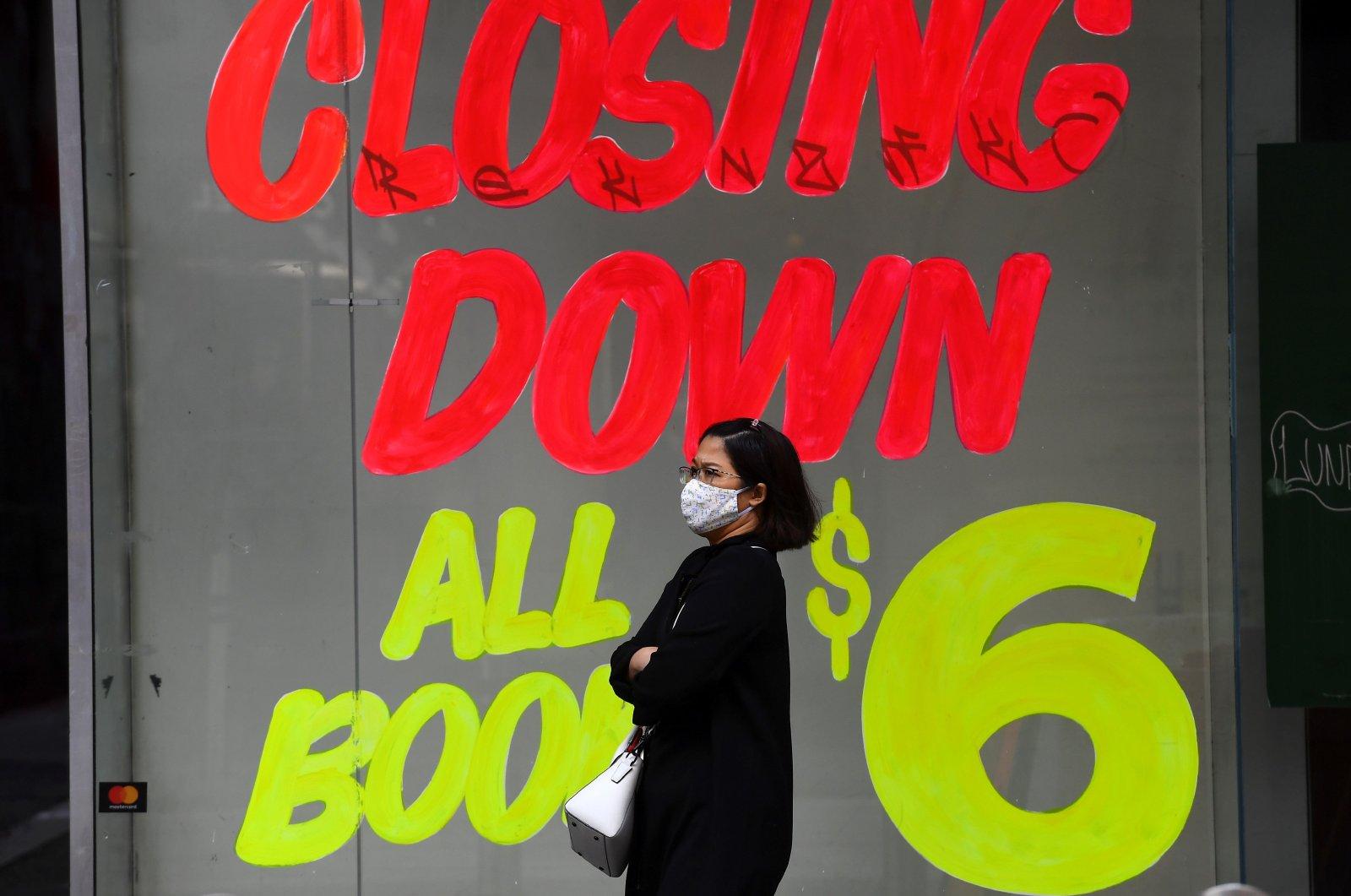 A woman walks past an empty shop in Melbourne's central business district, June 3, 2020. (AFP Photo)